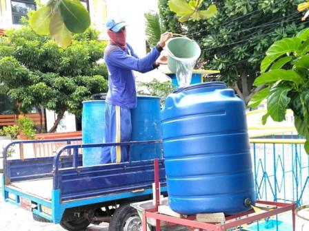 Petugas Mengisi Air Sarana Cuci Tangan di Lingkungan Pulau Pramuka
