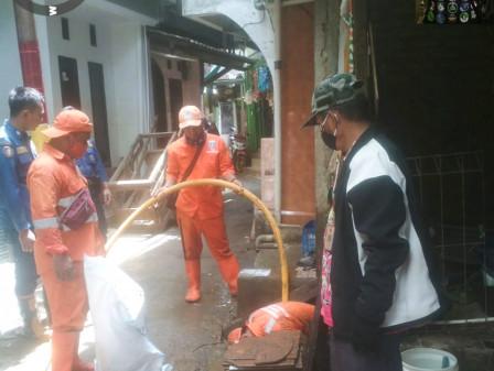 Petugas Gabungan Bersihkan Lumpur Sisa Banjir di Kampung Melayu