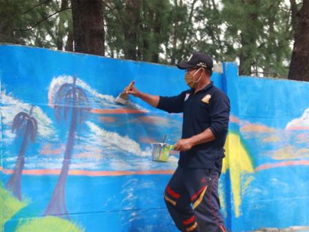 Tembok di Sepanjang Jalan Protokol Pulau Pramuka Dipercantik Dengan Mural
