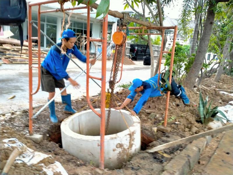 Proses pemasangan beton kedalam sumur resapan dibantu dengan alat