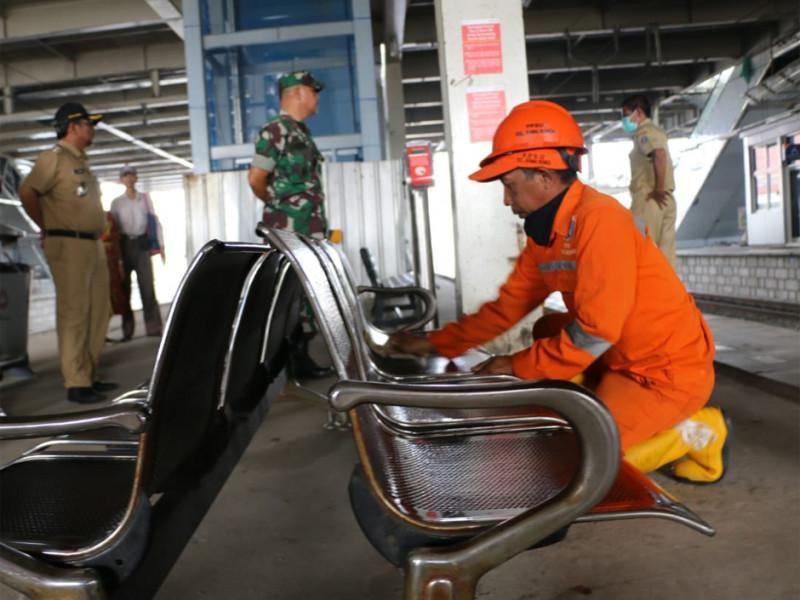 Petugas PPSU Kelurahan Rawa Bunga membersihkan bangku tempat menunggu penumpang di peron stasiun